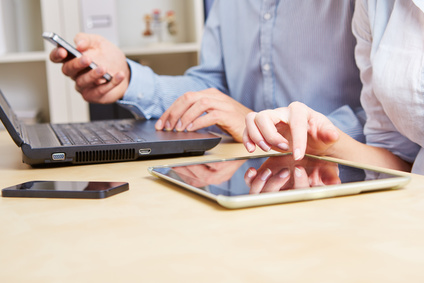 Business people using smartphones, tablets, and laptops