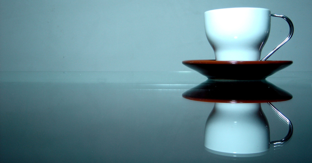 Coffee cup reflected on table, via Freeimages.com