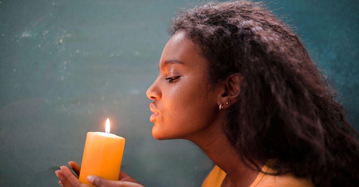 Woman holding burning candle, via Canva